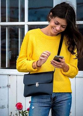 Crossover i sort med model i gul sweater
