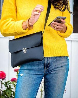 Crossover i sort med model i gul sweater closeup